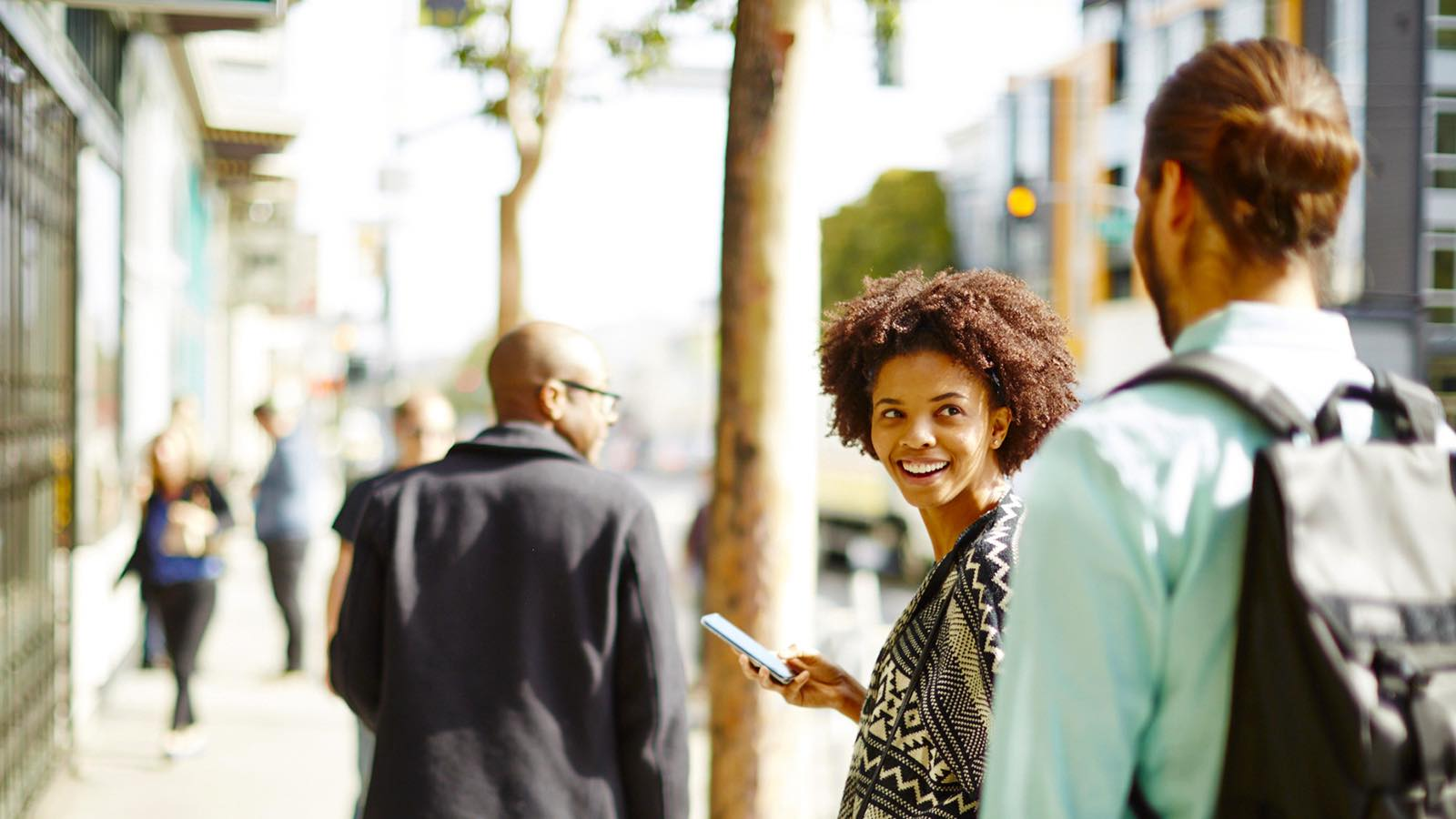 Woman holding a mobile phone, smiling at a person behind her.