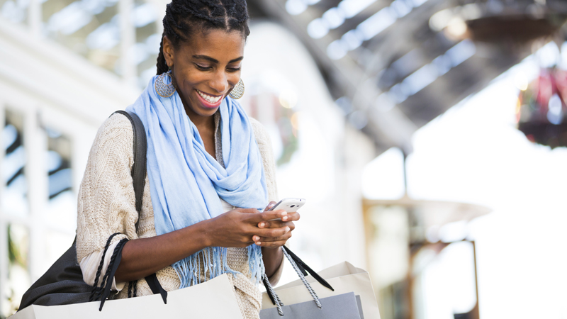 Woman in a scarf shopping with a phone