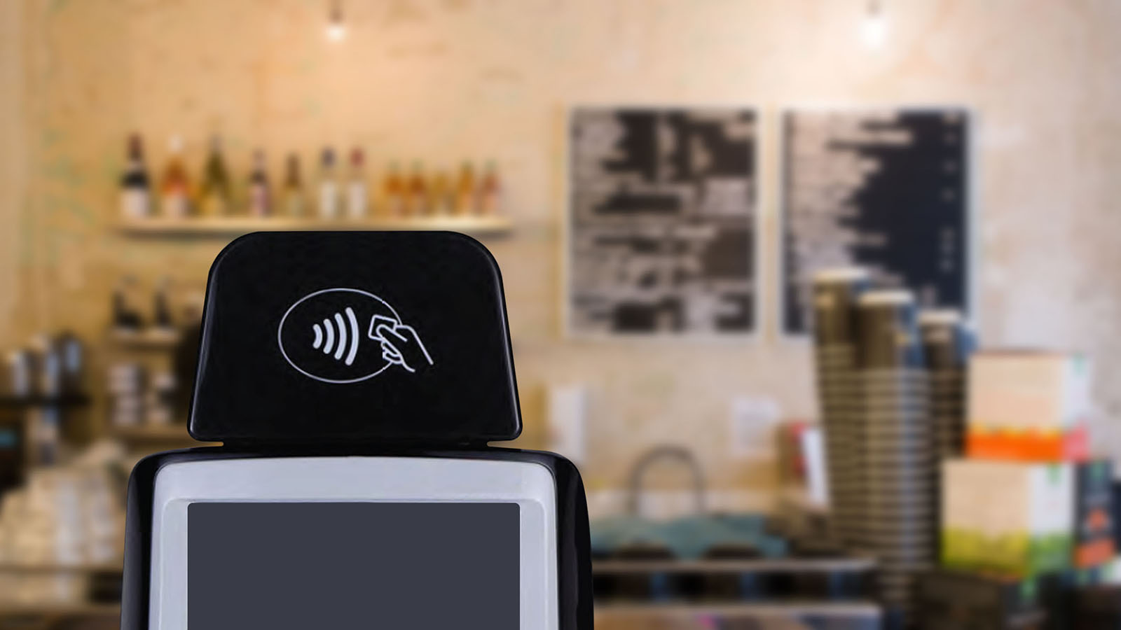 NFC terminal displaying contactless logo in a coffee shop.