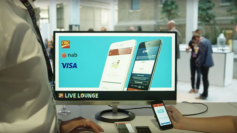 Two people talk in front of a computer screen showing Visa, CIBC, Nab logos and two phones in the CIBC Live Lounge.
